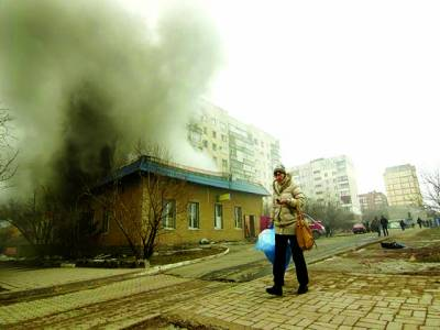 کیف: روسی حامیوں کی جانب سے حملے کے باعث عمارت سے دھواں اٹھ رہا ہے جبکہ ایک رہائشی خاتون پاس سے گزر رہی ہے