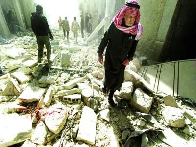 دمشق: شامی باشندے باغیوں کے حملے سے تباہ شدہ عمارتوں کے ملبے کے پاس کھڑے ہیں
