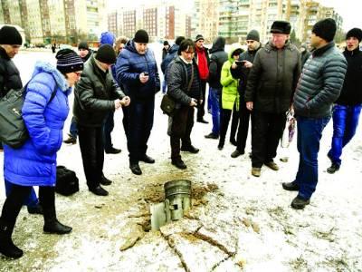 کیف: روسی حامیوں کی جانب سے حملے کے بعد یوکرینی باشندے راکٹ شیل کو دیکھ رہے ہیں