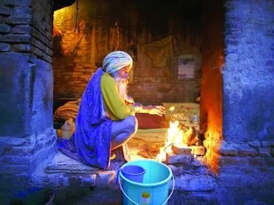 امرتسر:ایک شخص سردی سے بچاﺅ کیلئے آگ کے پاس بیٹھا ہے