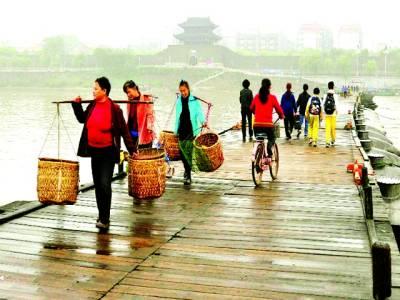 شنگھائی:لوگ قدیم پل پر سے گز ر کر جا رہے ہیں' لکڑی کے بنے ہوئے400 میٹر لمبے پل کو100کشتیاں سہارا دے رہی ہیں