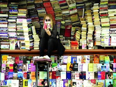 غزہ: ٖفلسطینی عورت اپنی دکان میں کتاب پڑھ رہی ہے