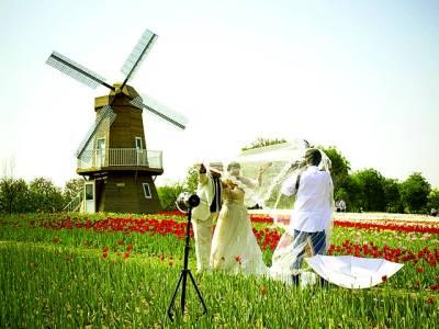 بیجنگ: نو بیاہتا جوڑا شینائی بین الاقوامی پھول میلہ میں تصویر کھنچوا رہا ہے