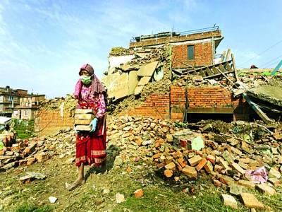 کھٹمنڈو: ایک خاتون زلزلے میں تباہ ہونے والے اپنے گھرکی اینٹیں اکٹھی کررہی ہے