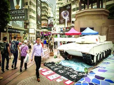 ہانگ کانگ: راہگیر نمائش کیلئے رکھے گئے ٹینک کے پاس سے گزر رہے ہیں