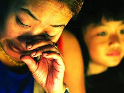 کوالالمپور: ملائشین طیارے میں ہلاک شدہ افراد کی یاد میں تعزیتی سیمینار میں ایک خاتون اپنے عزیز کی یاد میں رو رہی ہے