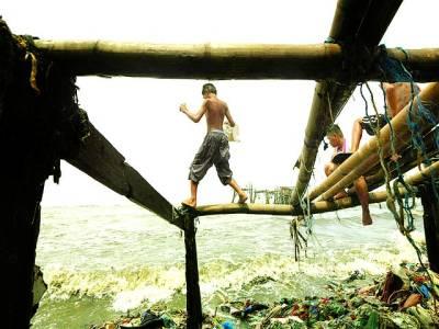 منیلا: بچے سمندر کنارے پائپوں پر کھیل رہے ہیں