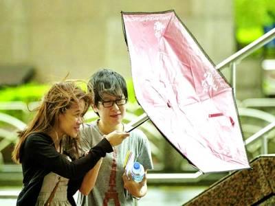 تائی پے:خاتون بارش سے بچاؤ کیلئے چھتری کھول رہی ہے