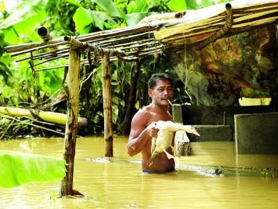 منیلا: ایک شخص سیلابی پانی میں بطخ کو پکڑے محفوظ مقام پر جا رہا ہے