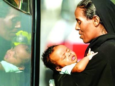 روم: اٹلی میں سمندری راستے سے آنے والی ایک تارک وطن خاتون اپنے بچے کے ہمراہ بس میں سوار ہورہی ہے