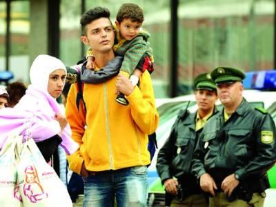 جرمنی: ایک شامی مہاجرخاندان کے نوجوان نے اپنے بچے کو کندھے پر اٹھارکھاہے