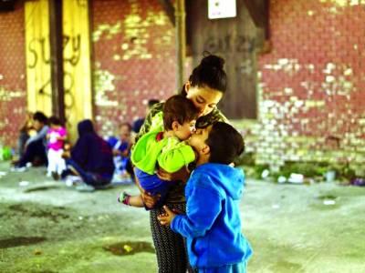 ہنگری کی سرحد کے قریب سرحد پارکرنے کے منتظر ایک شامی مہاجر خاندان کا بچہ اپنی چھ ماہ کی بہن کو پیار کررہاہے