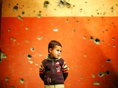 غزہ: فلسطینی بچہ اسرائیلی فوج کی فائرنگ سے نقصان زدہ مسجد کو دیکھ رہا ہے