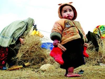 کابل: مہاجر کیمپ میں افغانی بچی اپنے جوتے پکڑی کھڑی ہے