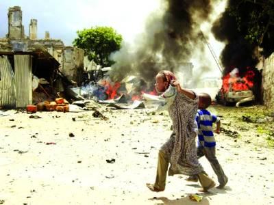 موغادیشو:نامعلوم افراد کی جانب سے لگی ہوئی آگ سے بچنے کیلئے ایک لڑکی بچے کے ہمراہ محفوظ مقام پر جانے کیلئے بھاگ رہی ہے