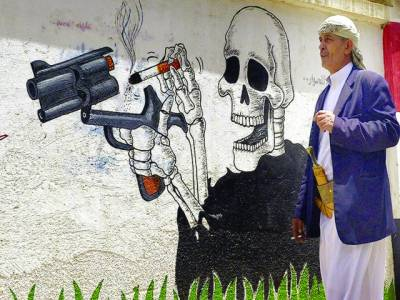 عیدن: یمنی شخص حکومت کی جانب سے دیوار پر کی گئی مہم 'نو سموکنگ' کے پاس سے گزر رہا ہے