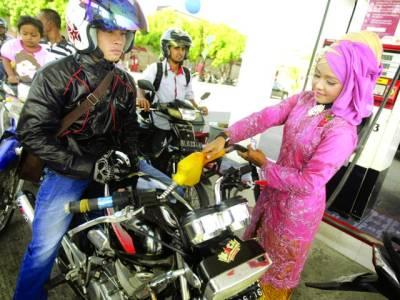 جکارتہ : انڈونیشین خاتون روائتی لباس پہنے موٹر سائیکل میں پٹرول ڈال رہی ہے