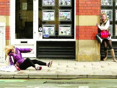 مانچسٹر:تیز ہوا کے باعث دو خواتین اپنا بچاؤ کر رہی ہیں