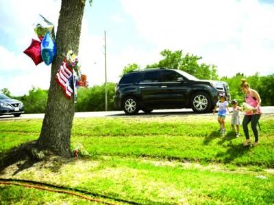 ٹیکساس: ایک خاتون اپنے بچوں کے ہمراہ سکول فائرنگ میں جاں بحق ہونے والوں کی یاد میں پھول رکھنے کیلئے آرہی ہے