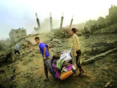 غزہ: فلسطینی اسرائیلی فوج کی بمباری سے تباہ شدہ عمارت سے اپنا سامان لیکر جارہے ہیں