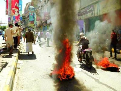 صنعاء: یمن کے شہر تعز میں احتجاج کے موقع پر لوگوں نے سڑک پر ٹائر جلا رکھے ہیں، ایک موٹر سائیکل سوار پاس سے گزر رہا ہے
