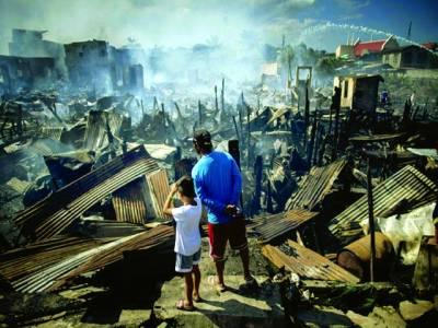 منیلا: فلپائن میں ایک شخص اپنے بچے کے ہمراہ آتش زدگی کے باعث تباہ ہونے والے گھروں کو دیکھ رہا ہے