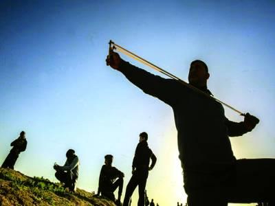 غزہ سٹی:فلسطینی مظاہرین غلیلوں کے ذریعے اسرائیلی فوجیوں پر پتھر پھینک رہے ہیں