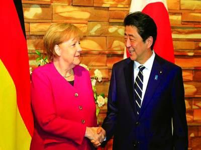 برلن: جرمن چانسلر اور جاپانی وزیراعظم ملاقات کے موقع پر ہاتھ ملا رہے ہیں